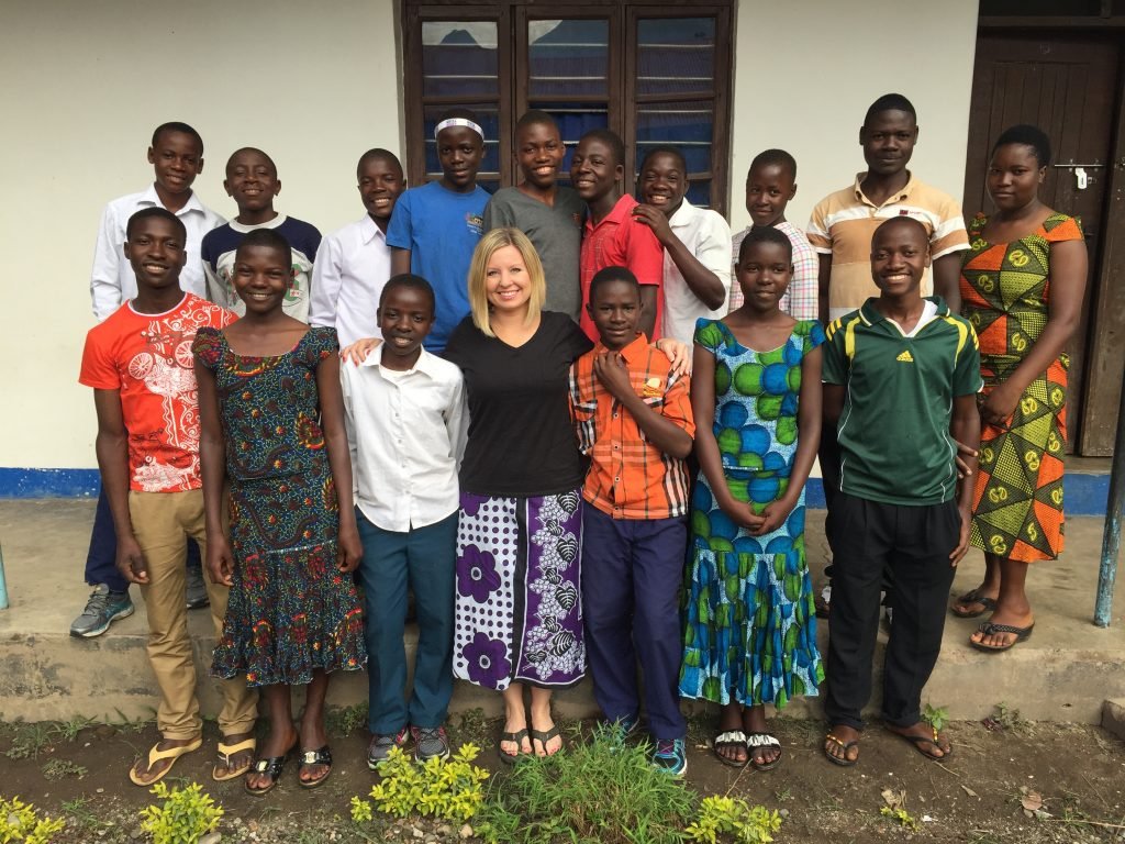 Tanzanian Missonary Mimi Henry poses for a picture with children from the orphanage.